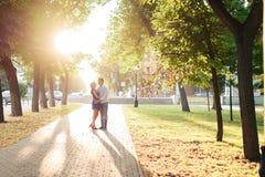 Härliga par som är förälskade med en kvinna som går i en parkera på en bänk som kysser på solnedgången och älskar sig, en blå klä Royaltyfria Bilder