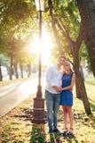 Härliga par som är förälskade med en kvinna som går i en parkera på en bänk som kysser på solnedgången och älskar sig, en blå klä Fotografering för Bildbyråer