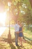 Härliga par som är förälskade med en kvinna som går i en parkera på en bänk som kysser på solnedgången och älskar sig, en blå klä Royaltyfri Foto