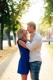 Härliga par som är förälskade med en kvinna som går i en parkera på en bänk som kysser på solnedgången och älskar sig, en blå klä Arkivfoton