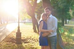 Härliga par som är förälskade med en kvinna som går i en parkera på en bänk som kysser på solnedgången och älskar sig, en blå klä Arkivbild
