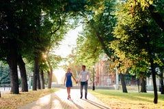 Härliga par som är förälskade med en kvinna som går i en parkera på en bänk som kysser på solnedgången och älskar sig, en blå klä Arkivbilder