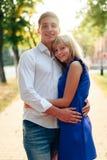 Härliga par som är förälskade med en kvinna som går i en parkera på en bänk som kysser på solnedgången och älskar sig, en blå klä Arkivfoto