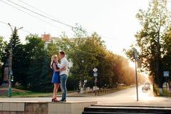 Härliga par som är förälskade med en kvinna som går i en parkera på en bänk som kysser på solnedgången och älskar sig, en blå klä Royaltyfria Foton