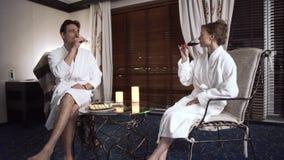 Härliga par som dricker alkohol som sitter på den lilla tabellen i modernt hotellrum arkivfilmer