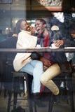 Härliga par som dricker kaffe och lyckligt skrattar royaltyfria bilder