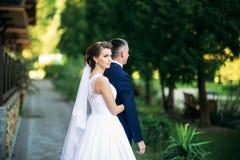 Härliga par som går i parkera i deras bröllopdag Fotografering för Bildbyråer