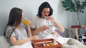 Härliga par som har frukosten i säng hemma med bakelse för kaffefruktfruktsaft arkivfilmer