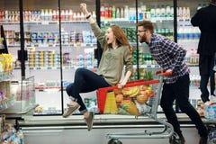 Härliga par som har gyckel, medan välja mat i supermarket royaltyfri fotografi
