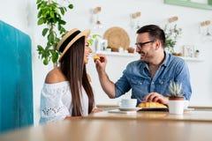Härliga par som har kaffe på ett datum och att ha gyckel tillsammans - Bild royaltyfri fotografi