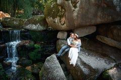 Härliga par som kramar nära en bergflod Arkivbilder