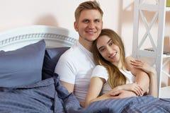Härliga par som kramar på säng i sovrum i morgonen, romanens och förälskelsen i förhållandebegrepp arkivbilder