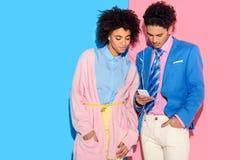 härliga par som lyssnar till musik på smartphonen på rosa färger och blått royaltyfria foton