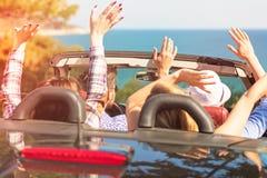 Härliga partivänflickor som dansar i en bil på den lyckliga stranden arkivbild