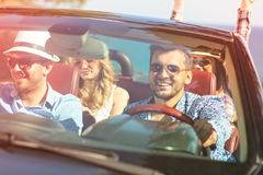 Härliga partivänflickor som dansar i en bil på den lyckliga stranden royaltyfri foto