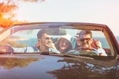 Härliga partivänflickor som dansar i en bil på den lyckliga stranden arkivbilder