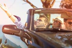 Härliga partivänflickor som dansar i en bil på den lyckliga stranden arkivfoton