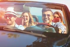 Härliga partivänflickor som dansar i en bil på den lyckliga stranden royaltyfria foton