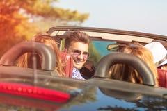 Härliga partivänflickor som dansar i en bil på den lyckliga stranden royaltyfri fotografi