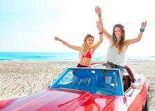 Härliga partivänflickor som dansar i en bil på stranden royaltyfri foto