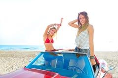 Härliga partivänflickor som dansar i en bil på stranden royaltyfri fotografi