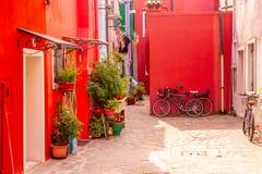 Härliga röda hus med cyklar F?rgrika hus i den Burano ?n n?ra Venedig, Italien arkivbilder