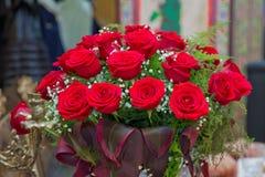 Härliga röda rosor i en rund ask Persikarosor i en rund ask Rosor i en rund ask på en vit träbakgrund Romantisk röd ro Fotografering för Bildbyråer