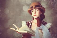 Härliga rödhårig mankvinnor med boken. Arkivfoto