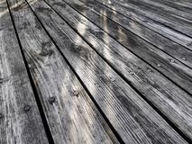 Härliga reflekterande diagonala band på trägolv med solljus fotografering för bildbyråer