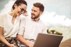 Härliga romantiska par genom att använda bärbara datorn royaltyfria bilder