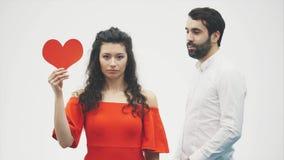 Härliga romantiska par som isoleras på vit bakgrund Attraktiv ung kvinna och stilig handkram med röd hjärta lager videofilmer