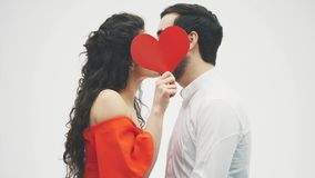 Härliga romantiska par som isoleras på vit bakgrund Attraktiv ung kvinna och stilig handkram med röd hjärta arkivfilmer