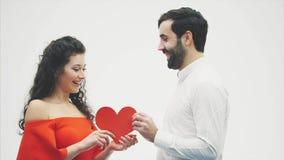 Härliga romantiska par som isoleras på vit bakgrund Attraktiv ung kvinna och stilig handkram med röd hjärta stock video