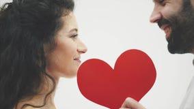 Härliga romantiska par som isoleras på vit bakgrund Attraktiv ung kvinna och stilig man Stänger den röda framsidan på