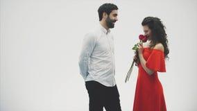Härliga romantiska par som isoleras på vit bakgrund En attraktiv ung kvinna som bär röda rosor i en klänning och lager videofilmer