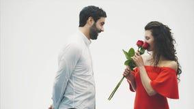 Härliga romantiska par som isoleras på vit bakgrund En attraktiv ung kvinna som bär röda rosor i en klänning och stock video