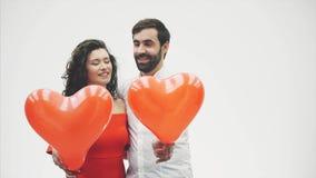 Härliga romantiska par som isoleras på vit bakgrund En attraktiv ung kvinna och härliga händer lyfter ballonger in arkivfilmer