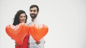 Härliga romantiska par som isoleras på vit bakgrund En attraktiv ung kvinna och härliga händer lyfter ballonger in stock video
