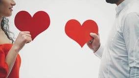 Härliga romantiska par som isoleras på vit bakgrund En attraktiv ung kvinna och en stilig hand rymmer röda hjärtor in