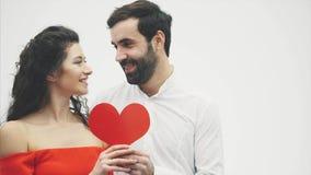 Härliga romantiska par som isoleras på vit bakgrund En attraktiv ung kvinna och en stilig man ger en röd hjärta lager videofilmer