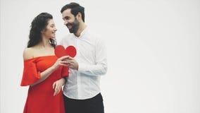 Härliga romantiska par som isoleras på vit bakgrund En attraktiv ung kvinna och en stilig man ger en röd hjärta