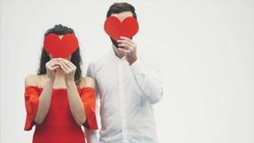 Härliga romantiska par som isoleras på vit bakgrund En attraktiv ung kvinna och en stilig man rymmer röda hjärtor in arkivfilmer