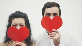 Härliga romantiska par som isoleras på vit bakgrund En attraktiv ung kvinna och en stilig man rymmer röda hjärtor in