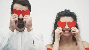 Härliga romantiska par som isoleras på vit bakgrund En iklädd attraktiv ung kvinna en röd klänning, en stilig man