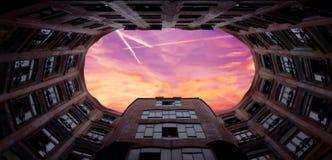 Härliga rosa färger och en röd solnedgång i ramen av en av Antonio GaudÃs mest fantastisk byggnader Arkivfoton