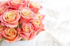 Härliga rosa rosor i en rund ask Persikarosor i en rund ask Rosor i en rund ask på en vit träbakgrund Royaltyfri Fotografi
