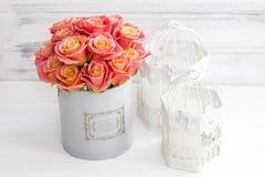 Härliga rosa rosor i en rund ask Persikarosor i en rund ask Rosor i en rund ask på en vit träbakgrund Royaltyfria Bilder