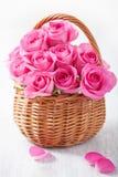 Härliga rosa rosor i korg Arkivfoto