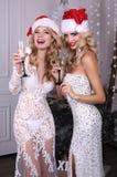 Härliga sexiga flickor med blont hår i lyxiga klänningar, hållande exponeringsglas av champagne i händer, Arkivbilder