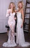 Härliga sexiga flickor med blont hår i lyxiga klänningar, hållande exponeringsglas av champagne i händer, Fotografering för Bildbyråer